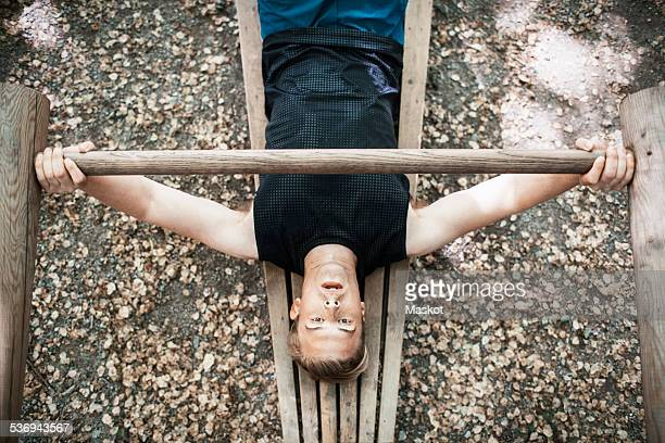 High angle view of man lifting wooden weight at outdoor gym
