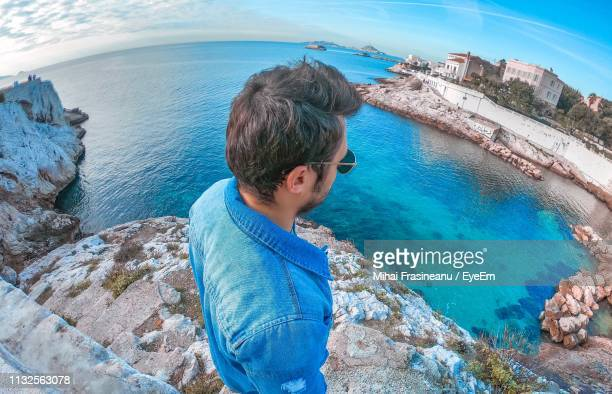 high angle view of man looking at sea against sky - marseille stock pictures, royalty-free photos & images
