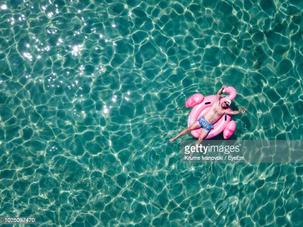 high angle view of man lying in inflatable ring on swimming pool - inflatable raft stock pictures, royalty-free photos & images