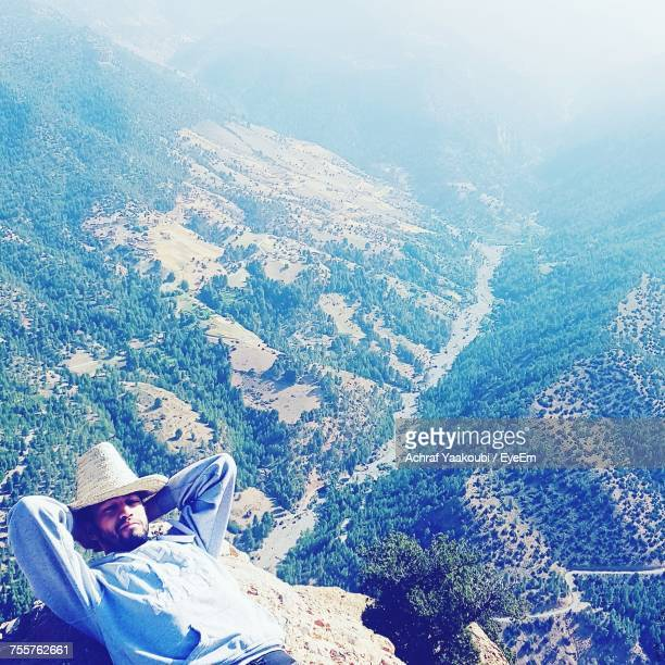 High Angle View Of Man Lying On Cliff Against Mountains During Winter
