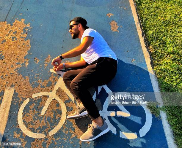 high angle view of man lying on road with bicycle symbol - fahrrad stock-fotos und bilder