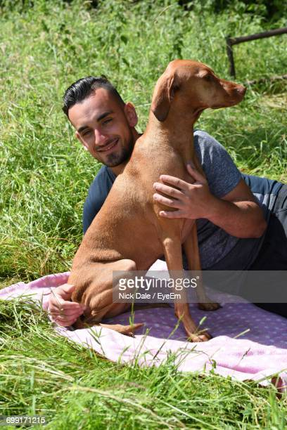 High Angle View Of Man Lying With Vizsla On Picnic Blanket At Park