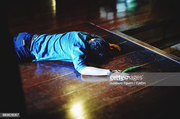 high angle view of man murdered on hardwood floor - dead body stockfoto's en -beelden