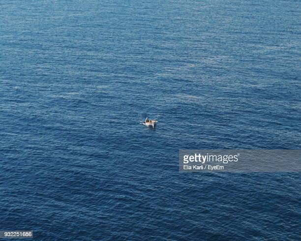 high angle view of man on boat sailing in sea - elia karli stock-fotos und bilder