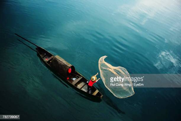 high angle view of man on boat throwing fishing net - asian style conical hat stock pictures, royalty-free photos & images