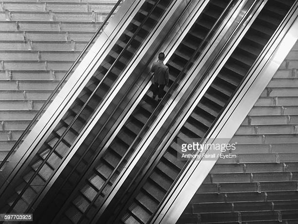 High Angle View Of Man On Escalator In Modern Building