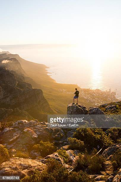 High Angle View Of Man On Rock Looking At Sea
