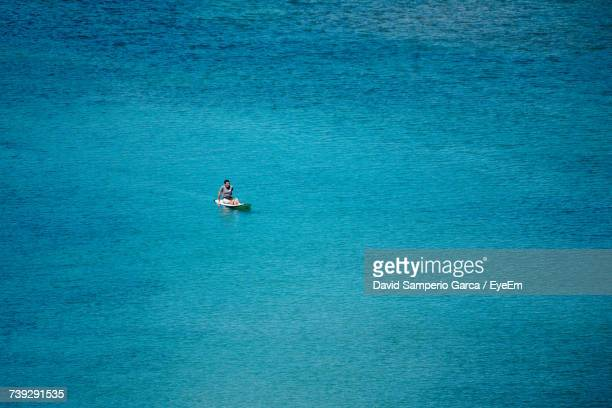 High Angle View Of Man On Surfboard At Turquoise Sea