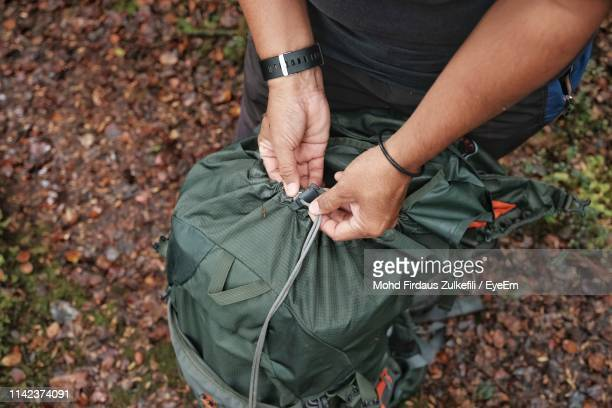 high angle view of man opening backpack on field - open backpack stock pictures, royalty-free photos & images