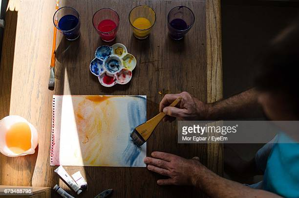 High Angle View Of Man Painting Paper At Wooden Table