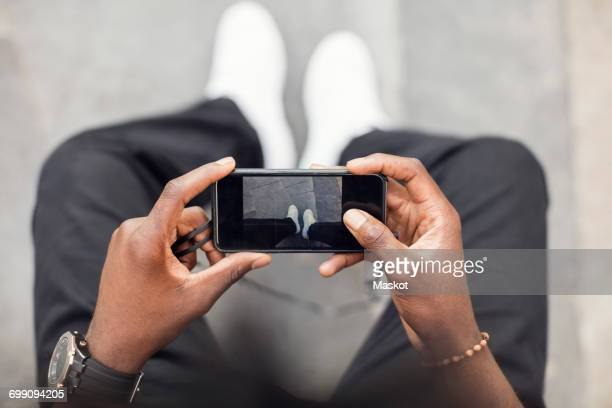 High angle view of man photographing legs on mobile phone