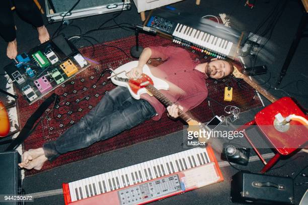 high angle view of man playing guitar while lying on carpet at studio - musiker stock-fotos und bilder