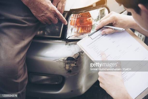 high angle view of man pointing at damaged car by agent holding papers - car insurance stock pictures, royalty-free photos & images