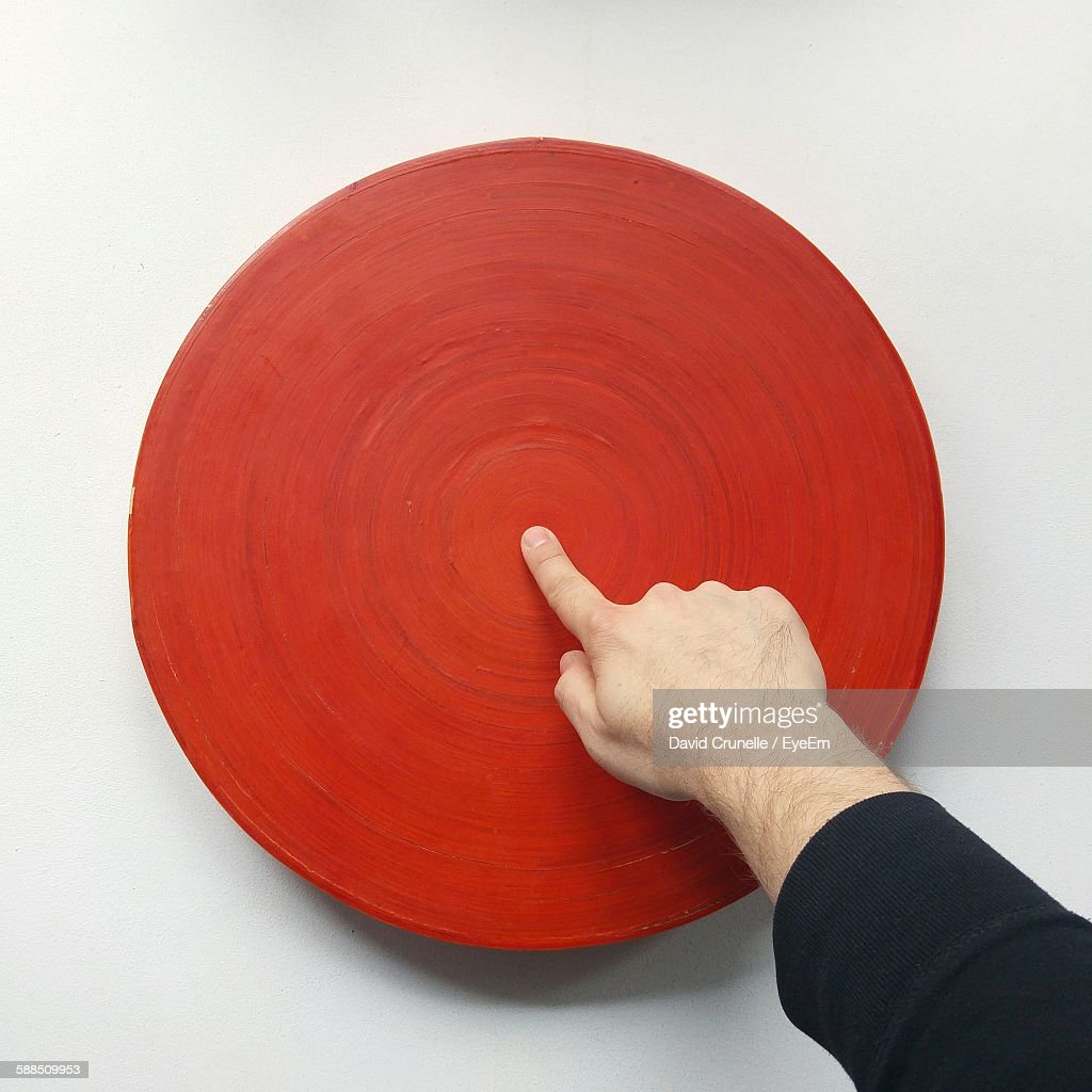 High Angle View Of Man Pointing At Red Circle Center Against White Background : Stock Photo