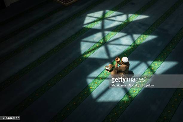 high angle view of man praying in mosque - muslim praying stock pictures, royalty-free photos & images