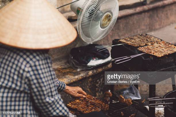high angle view of man preparing food on barbecue grill - bortes stock-fotos und bilder