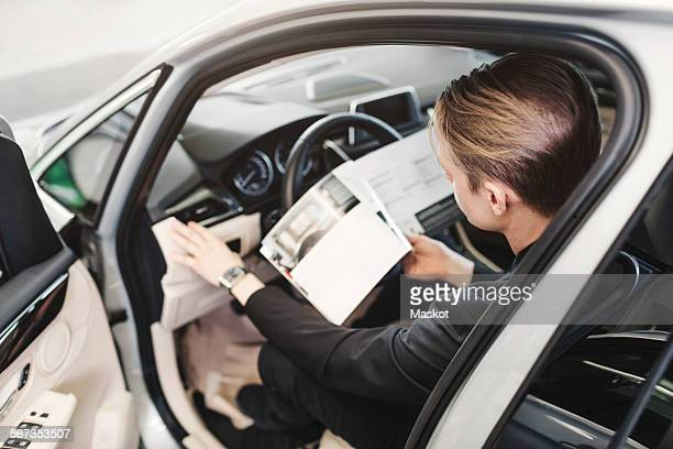 High angle view of man reading brochure while sitting in car at store