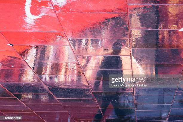 high angle view of man reflecting on wet footpath - mcgregor stock pictures, royalty-free photos & images