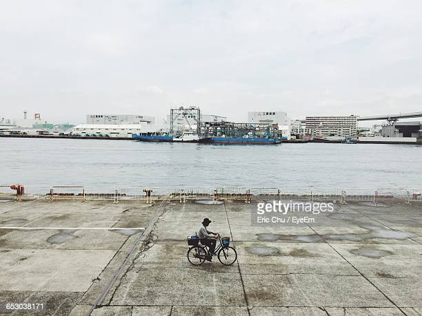 High Angle View Of Man Riding Bicycle On Walkway Against River At Harbor