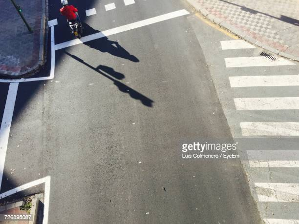 high angle view of man riding motor scooter on street in city - zebra crossing stock pictures, royalty-free photos & images