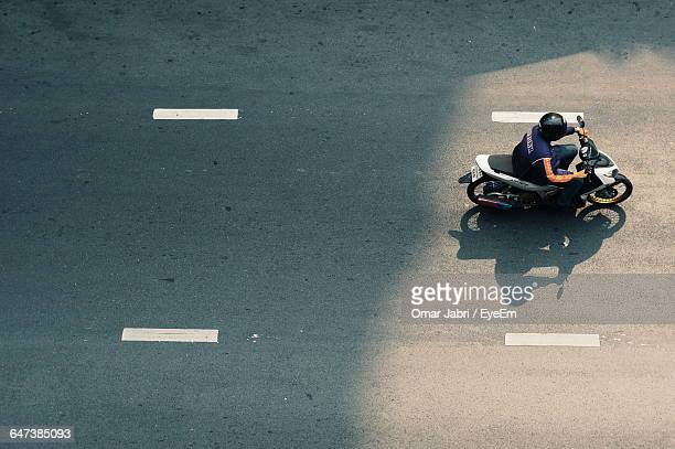 High Angle View Of Man Riding Motor Scooter On Street