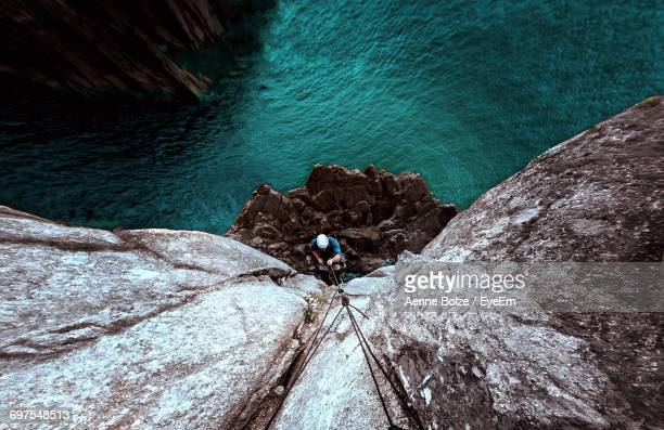 high angle view of man rock climbing - arrampicata su roccia foto e immagini stock