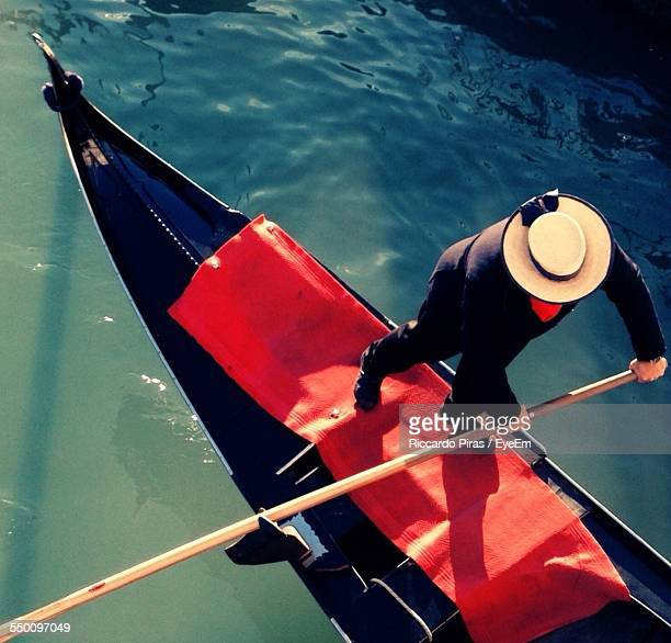 high angle view of man rowing gondola on lake - gondola traditional boat stock pictures, royalty-free photos & images