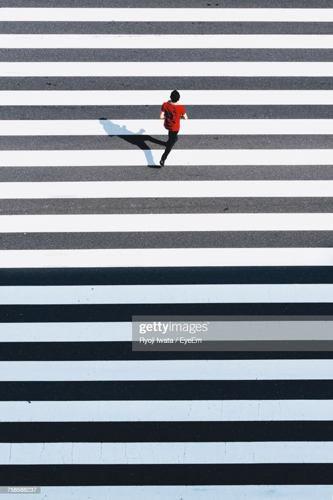 High Angle View Of Man Running On Zebra Crossing : Stock Photo