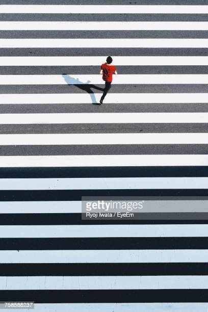 high angle view of man running on zebra crossing - pedestrian crossing stock photos and pictures