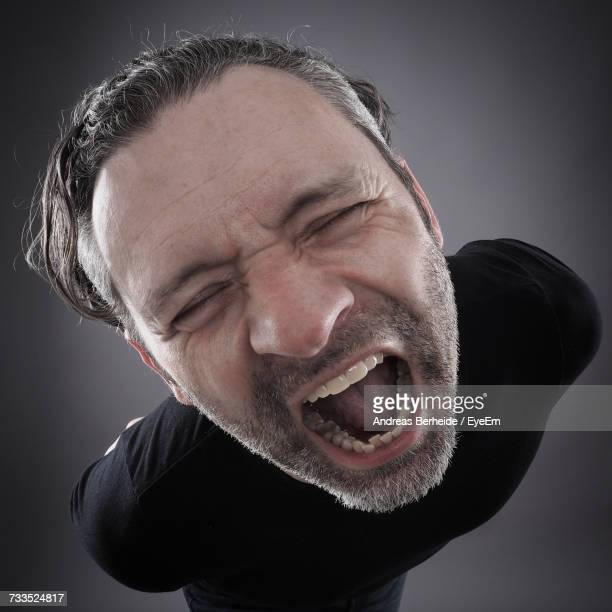 High Angle View Of Man Screaming Against Black Background
