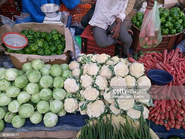 high angle view of man selling vegetables at market - moringa oleifera stock photos and pictures