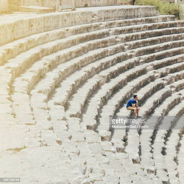 high angle view of man sitting at roman theater - amphitheater stock photos and pictures