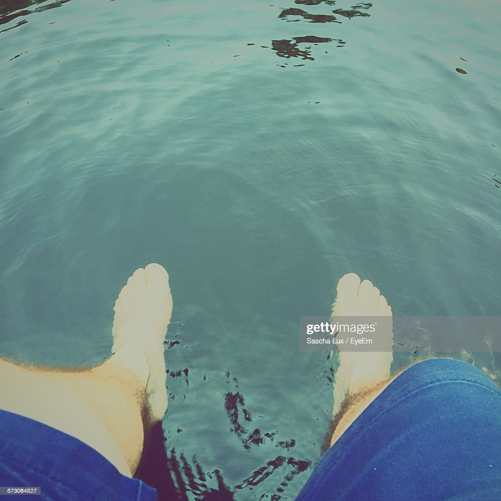 High Angle View Of Man Sitting By Pond With Feet In Water At Berlin Zoological Garden : Stock Photo
