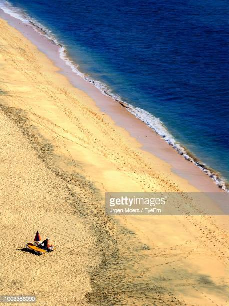 High Angle View Of Man Sitting On Beach