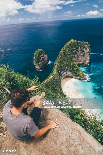 high angle view of man sitting on cliff against sea - insel nusa penida stock-fotos und bilder