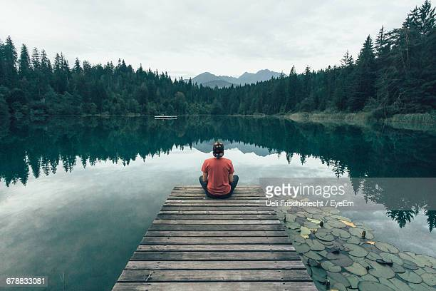 high angle view of man sitting on pier over lake - ambientazione tranquilla foto e immagini stock