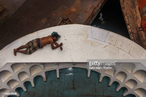 high angle view of man sleeping on boat - dhaka stock pictures, royalty-free photos & images