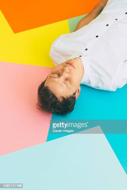 high angle view of man sleeping on colorful blank papers - pop art stock pictures, royalty-free photos & images