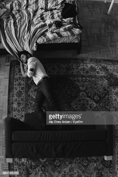 High Angle View Of Man Sleeping On Floor At Home
