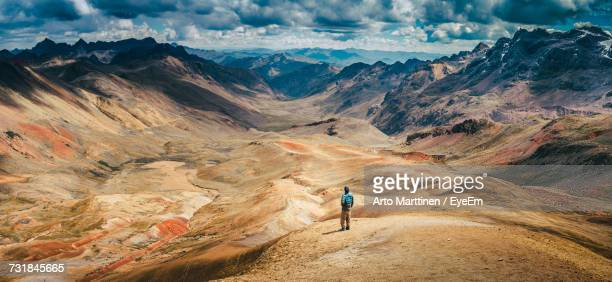 high angle view of man standing at altiplano against cloudy sky - südamerika stock-fotos und bilder