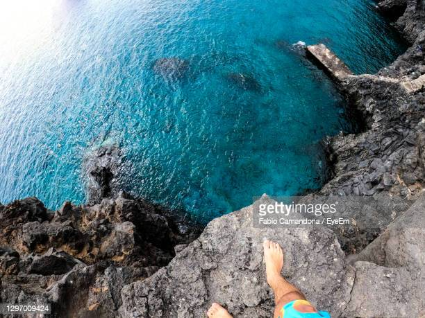 high angle view of man standing at cliff edge by sea - human foot stock pictures, royalty-free photos & images