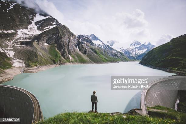 high angle view of man standing on cliff against kaprun dam during winter - reservoir stock pictures, royalty-free photos & images