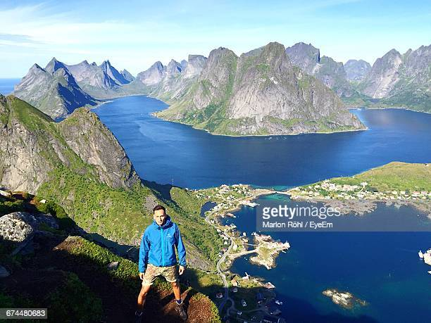 High Angle View Of Man Standing On Mountain Against Sea At Moskenesoya