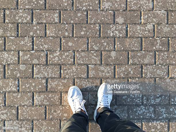 High Angle View Of Man Standing On Pavement