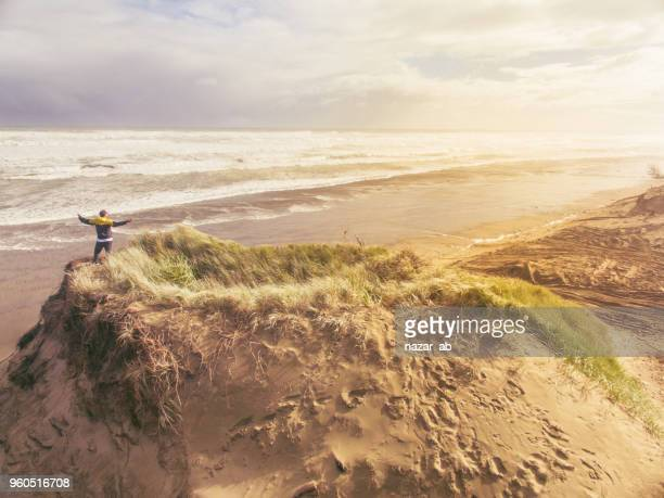 High angle view of man standing on sand dune with open arms looking across the beach.