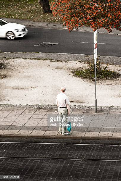 High Angle View Of Man Standing On Sidewalk