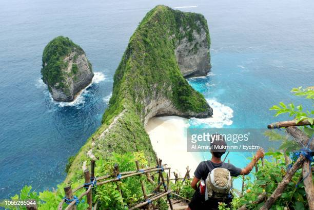 high angle view of man standing on steps over sea - bali stock-fotos und bilder