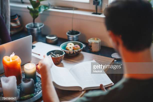 High angle view of man studying book in college dorm room