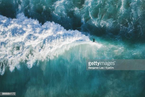 high angle view of man surfing in sea - bewegung stock-fotos und bilder