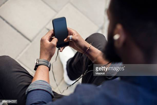 high angle view of man surfing the net on mobile phone - over the shoulder view stock pictures, royalty-free photos & images